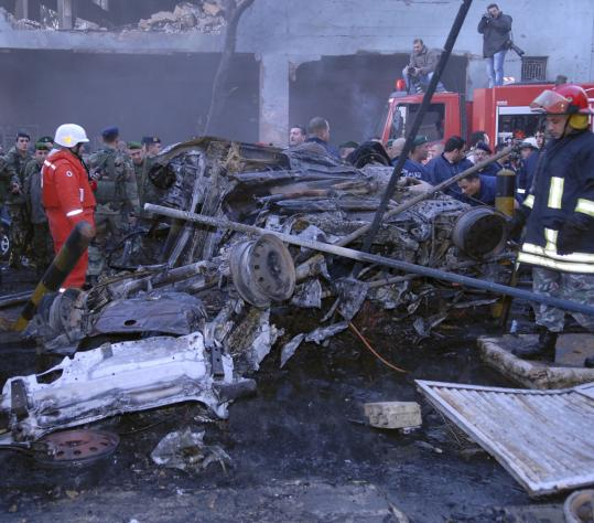 Lebanese soldiers and Red Cross workers searched charred cars at the site of bomb blast in northern Beirut yesterday. A sport utility vehicle from the US embassy was called the target.