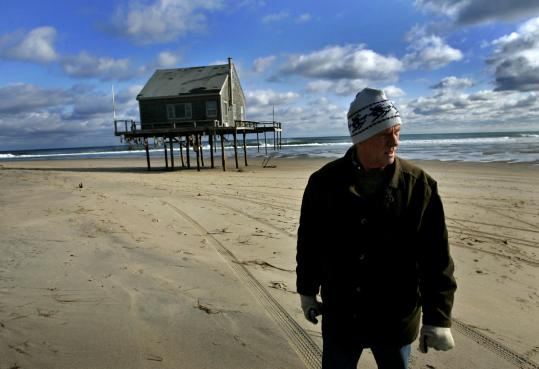 Fred Truelove walked on the beach by his home on North Beach in Chatham, which is scheduled to be torn down before it is washed away by the ocean.