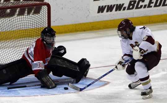 Catholic Memorial goalie Tom Conlin uses his stick to block this shot by BC High forward PJ Martina.