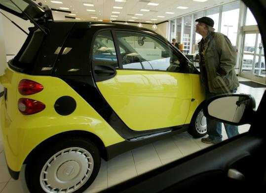 A Smart Fortwo car gets the once-over at a dealership in Bloomfield Hills, Mich., yesterday. Smart is a division of Daimler AG's Mercedes-Benz brand. Its cars have been sold in Europe for nearly a decade.
