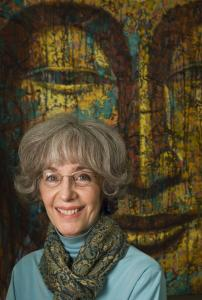 Lowell artist Virginia Peck stood in front of one of her seven paintings in the 'Buddha Room' at Gallery Anthony Curtis in Boston. They all feature the meditative face of the Buddha