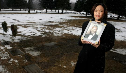 LaShell Drake held a picture of her grandfather, Booker Townsell, at his grave Thursday in Milwaukee. The military set aside its court-martial of Townsell.