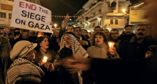Palestinians held candles and banners during a demonstration in support of Gaza, in the West Bank city of Ramallah yesterday. Israel will allow some fuel, medicine, and food into Gaza Strip.