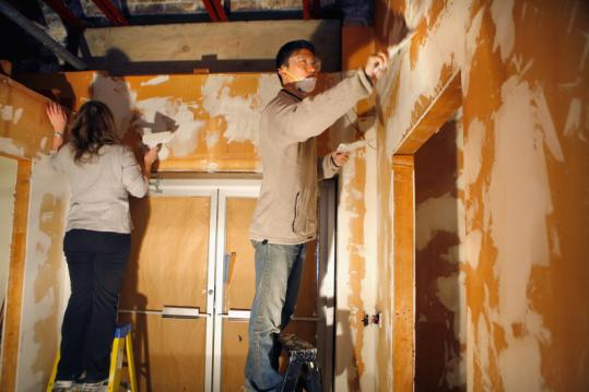 Volunteers Michelle Barbera and Robert Woo work on the walls of ImprovBoston's new home in Central Square.