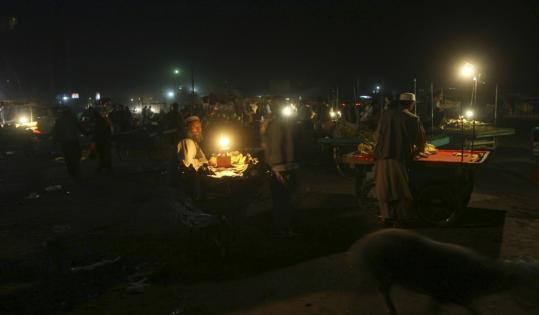 Vendors at a bazaar in Kabul in September. More than five years after the fall of the Taliban, dinner by candlelight remains common in the Afghan capital.