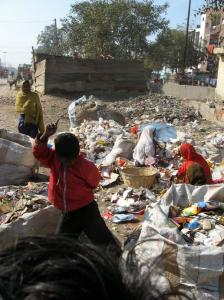 A boy danced as his mother sorted through garbage, an occupation reserved for the lower castes, in New Delhi.