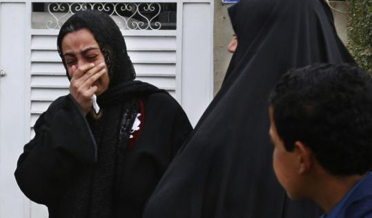 Neighbors wept yesterday outside the house where a former Baghdad city official was stabbed to death along with his wife and daughter in Talbiyah, a mostly Shi'ite neighborhood.
