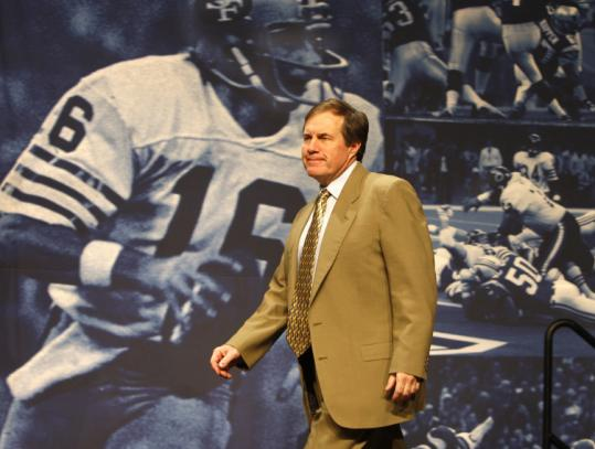 Bill Belichick, who appreciates the history of the game, strides past a huge montage of star players from Super Bowls past.
