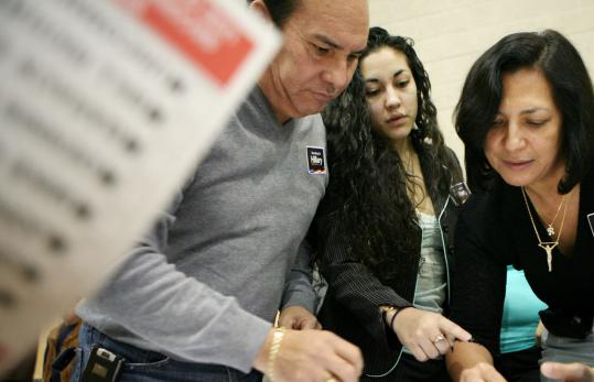 Reynaldo Salas (left) with daughter Blanca, and wife Reyna, looked over paperwork before voting Jan. 19 in Las Vegas.