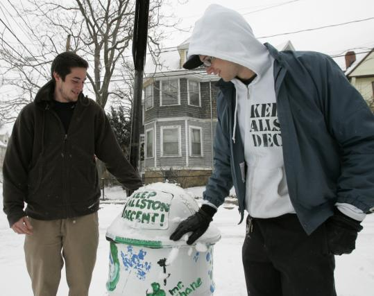 Alex Owens (left) and Charlie Geyer at a trash can painted with 'Keep Allston Decent,' the name of their group, whose roughly 14 members clean up their neighborhood after rowdy parties.
