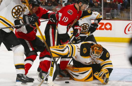 Tim Thomas (30 saves) is able to cover up as the Senators' Chris Neil (left) and Jason Spezza go after a loose puck.