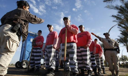 Male chain gang workers wear pink underwear, black-and-white striped pants, and pink T-shirts.