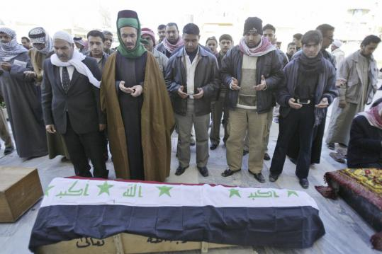 Relatives prayed for a soldier, Azhar Kamil, 24, during his funeral yesterday in Najaf, Iraq. Kamil was killed in Friday's bombing in Baghdad. Officials raised the death toll to at least 99.