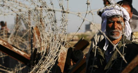 A Palestinian man looked through barbed wire yesterday at the newly closed border between Gaza and Egypt, in Rafah, southern Gaza Strip.