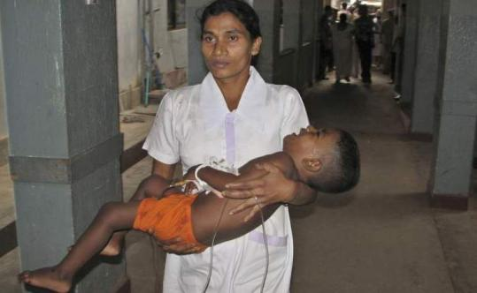A medical assistant at a hospital in Anuradhapura, Sri Lanka, carried a survivor of the roadside bombing of a bus yesterday.