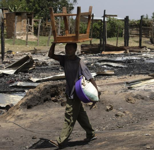 A man walked by a burned market in Sotik, Kenya yesterday. Violent conflict continues, having taken more than 1,000 lives and forced many to flee their homes.