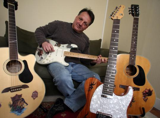 Mike DeCarlo with guitars decorated with removable stickers he is marketing as Tat-Paks.