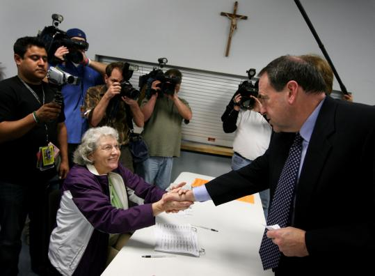 Republican presidential hopeful Mike Huckabee greeted a poll worker before he voted yesterday in North Little Rock, Ark.