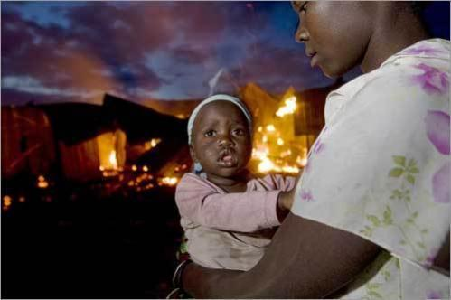 A resident of a shanty town in the western Kenyan town of Kericho holds her daughter as they watch their home go up in flames after members of the Kikuyu tribe set it ablaze during ethnic clashes in a further blow to hopes raised by a peace deal between political rivals.