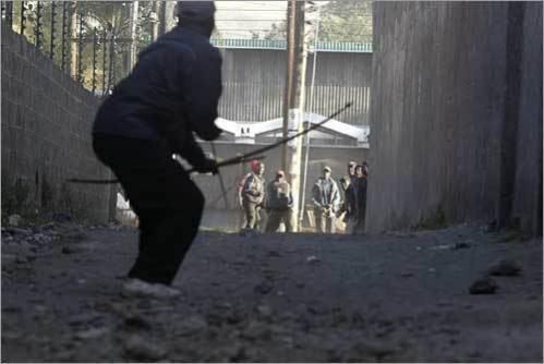 A lone member of the Luo tribe uses his bow and arrows to keep members of the Kikuyu tribe (background) at bay during ethnic clashes in the central Kenyan town of Nakuru. Marauding gangs armed with machetes, metal bars, and bows and arrows stalked parts of the west of the country.