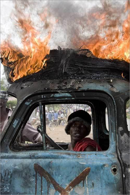 A man belonging to the Luo tribe and a supporter of Kenya's opposition leader Raila Odinga sits inside a destroyed vehicle with a burning tire on its roof during ethnic clashes in the Western Kenyan town of Kisumu.