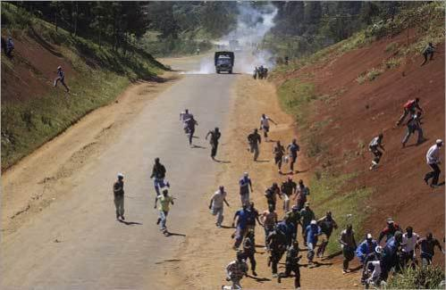 Men belonging to the Kikuyu tribe run away from an approaching police truck after the mob had blocked the main road connecting Kenya's capital with the town of Naivasha. The police dispersed the Kikuyu mob by using tear gas and firing in the air. Kenyan police have been given orders to shoot to kill in a bid to stem weeks of violence, a police commander said.