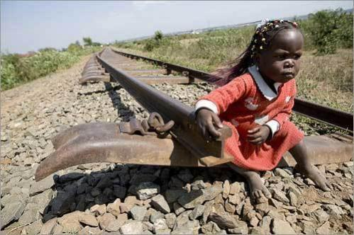 A girl sits on a part of the train rail that connects Kenya with its western neighbor Uganda after a crowd destroyed the tracks in the Western Kenyan town of Kisumu.