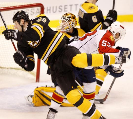 The Bruins' Zdeno Chara hits the ice after colliding with the Panthers' Brett McLean in front of the Boston net.