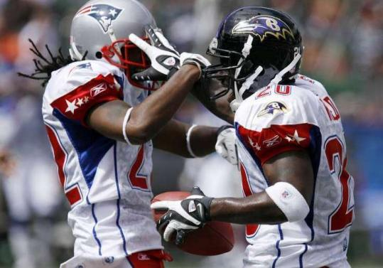 The Patriots' Asante Samuel (left) shows some AFC spirit after Baltimore's Ed Reed recovered a fumble in the first quarter.