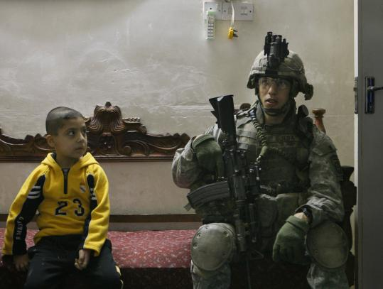 A boy looked at a US soldier during a house search yesterday in north Baghdad. The US military in northern Iraq confirmed an attack on a compound housing its Sunni allies against Al Qaeda in Iraq near Sinjar, about 60 miles west of Mosul.
