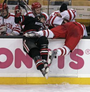 NU's Dennis McCauley hits the boards and BU's Colby Cohen goes over them in the third.