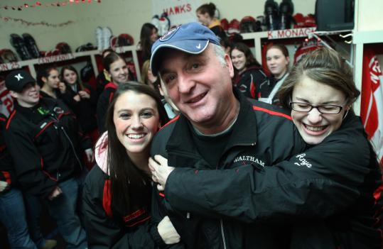 Waltham High hockey players Dana Centofanti (left) and Anya Battagoino show the team's appreciation for assistant coach George Tedford, who was among the squad's fathers who built their locker room at Veterans Memorial Rink.