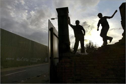 Two boys play on an old bombed-out army barracks wall next to the ever-present 'Peace Walls' which divide the Interface areas in Belfast, Northern Ireland. Without the Peace Walls, daily life would not be possible for the Catholic and Protestant families who live on each side of the physical divide. Even today, years after the signing of the Good Friday Peace Agreement, the walls have had to be expanded upward to provide protection from the rocks, bottles and occasional petrol bomb that continue to be thrown by both sides.