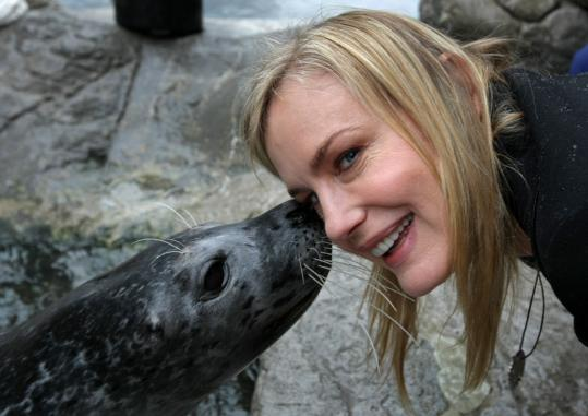 Actress Daryl Hannah cuddles up with Chuck, an Atlantic harbor seal, at the New England Aquarium yesterday.