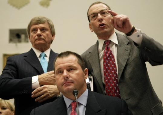 Roger Clemens listens as his attorneys - Rusty Hardin (left) and Lanny Breuer - try to address committee members on Capitol Hill.