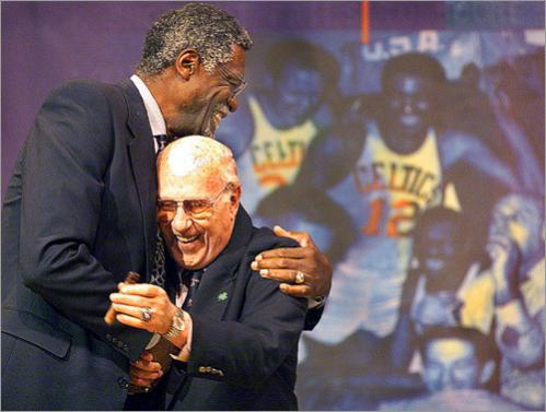Buy this picture! With an old photo of the two of them celebrating a championship in the backround, Red Auerbach greets Bill Russell as #6 comes onto the stage at his 1999 tribute.