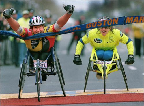 Buy photographs by Jim Davis Louise Sauvage of Australia raises her arms in victory as she leaves Jean Driscoll of Illinois in open mouthed disbelief, capturing the Women's Wheelchair division of the 1998 Boston Marathon. The finish was so close that both women had official times of 1:41:19. Driscoll came down Boylston Street thinking that she had the race won. Even the public address announcer didn't know that Sauvage was closing in on Driscoll, who was starting to raise her own arms in victory, but never got the chance.