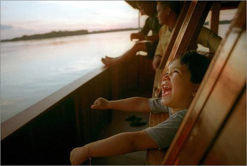 Four-year old Madson da Silva Araujo sticks his head out the bridge of his father's boat near the Equator along the Rio Branco in Brazil. The boat is Madson's playground and the crew are his playmates.