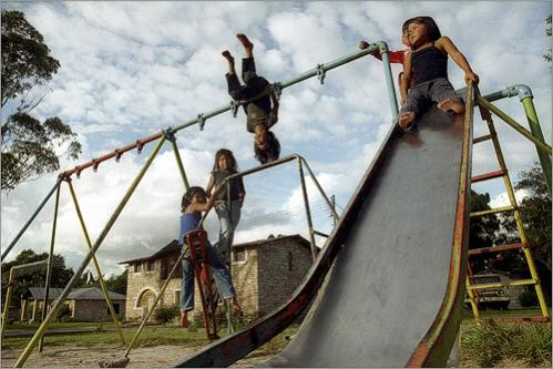 Children from the village of Kavanayen, Venezuela play on a swing as the day comes to a close. The Indian community was westernized by Capuchin monks who taught the natives how to build stone houses.