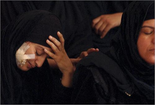 While sitting with relatives in her home in Saddam City, Iraq, (now known as Revolution City) Fatima Hamid mourns while still carrying a piece of shrapnel in her jaw from the same Fedayeen attack which killed three of her children and her sister-in-law two weeks earlier.