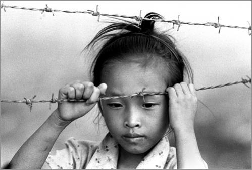 Buy this picture! A young refugee leans on barbed wire inside Phanat Nikom refugee camp in Thailand in 1987.