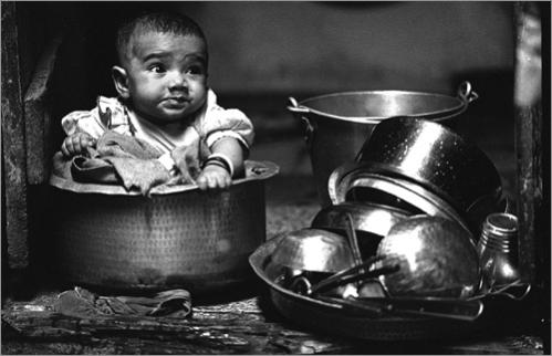 Buy this picture! A baby girl sits in a cooking pot while her mother works around their home in Bombay, India.