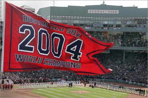 Buy this picture! The Boston Red Sox and the New York Yankees line up after introductions for the National Anthem with the championship flag flying from the center field flag pole during the Sox home opener in 2005.