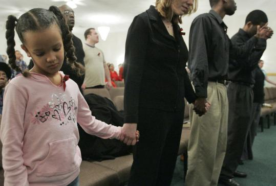 Six-year-old Maria Wright held hands with her mother, Liz, as the congregation prayed at the Cathedral of Praise Church in DeKalb, Ill. The service was dedicated to the victims of the campus shooting at Northern Illinois University.