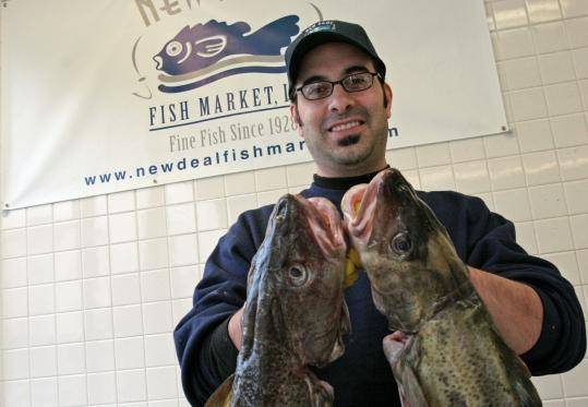 Carl Fantasia, owner of the New Deal in Cambridge, holds up some local cod. Dried and salted or fresh, the fish makes a flavorful meal any time of year.