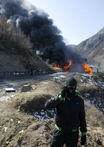 A protester talked on a mobile phone after Kosovo Serbs burned down a border crossing in Jarinje yesterday.