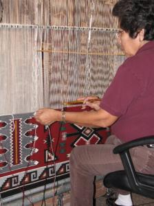 A Navajo woman weaves a rug on a traditional loom.