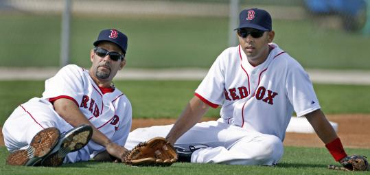 Taking a relaxed approach, Mike Lowell (left) and Alex Cora hone their observational skills during yesterday's Red Sox workout.