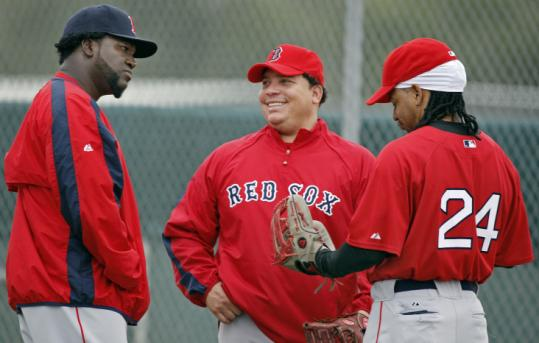 Bartolo Colon (center) chats with David Ortiz (left) and Manny Ramírez, whose presence helped persuade him to join the Sox.