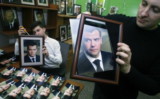 Shopkeeper Vladimir Tyshko (right) prepared a portrait of presidential candidate Dmitry Medvedev for sale Friday in Moscow. Medvedev is widely expected to defeat a weak field.